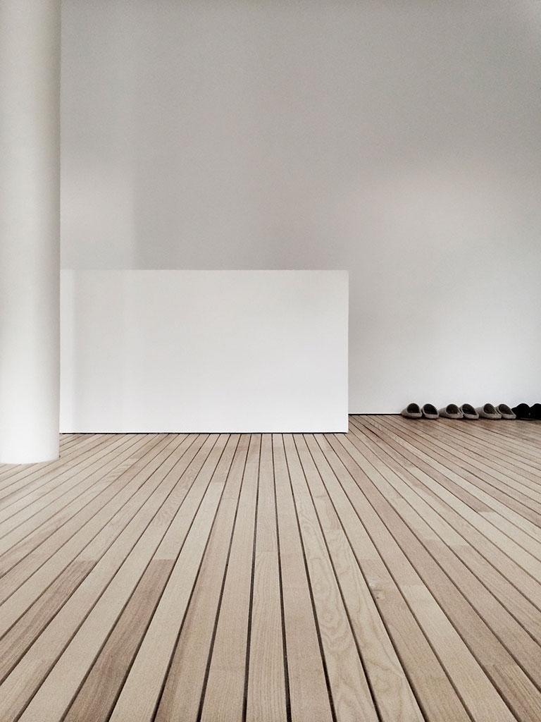 weniges, gedämpftes licht von aussen prägt am tag den raum. ruhe und konzentration resultieren aus dieser stillen, diffusen atmosphäre.