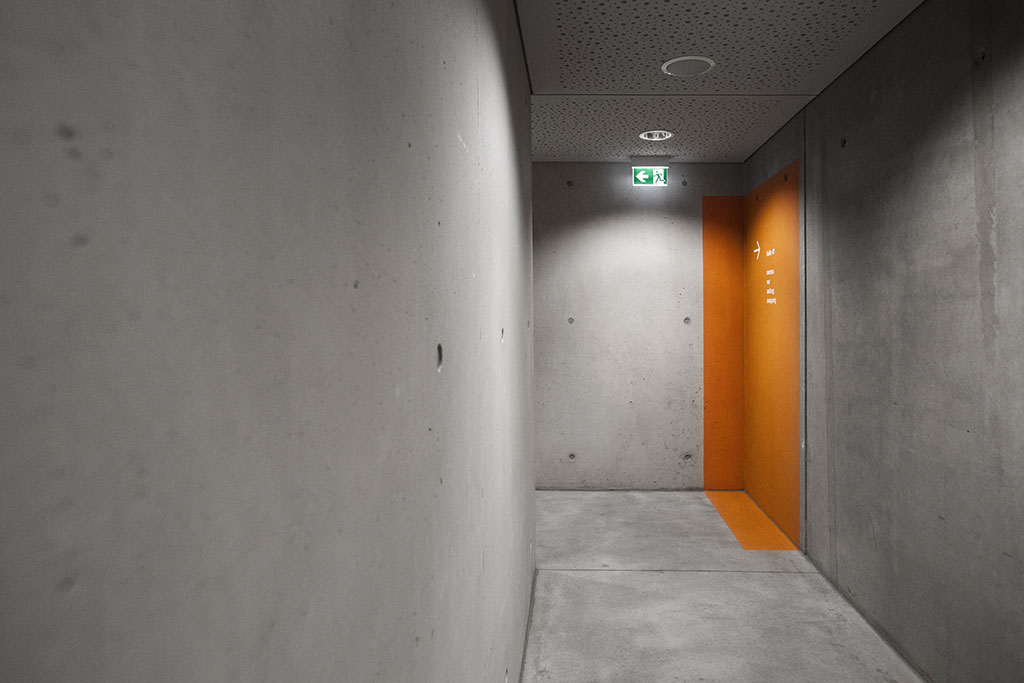 oranges farbfeld schmiegt sich in die architektur und rutscht in seiner anlage durch die raumecke und auf den boden